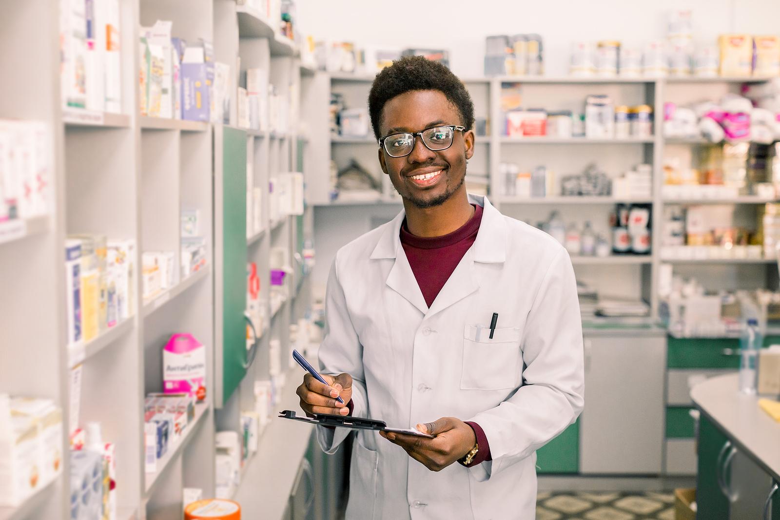 Pharmacy technician holding clipboard in pharmacy.